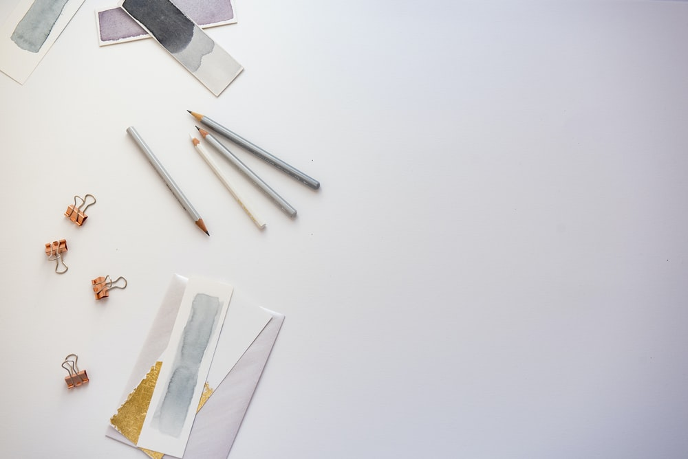 high angle photo of four pencils and greeting card