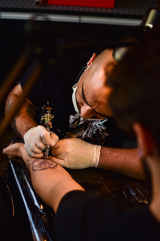 man doing tattoo on human arm