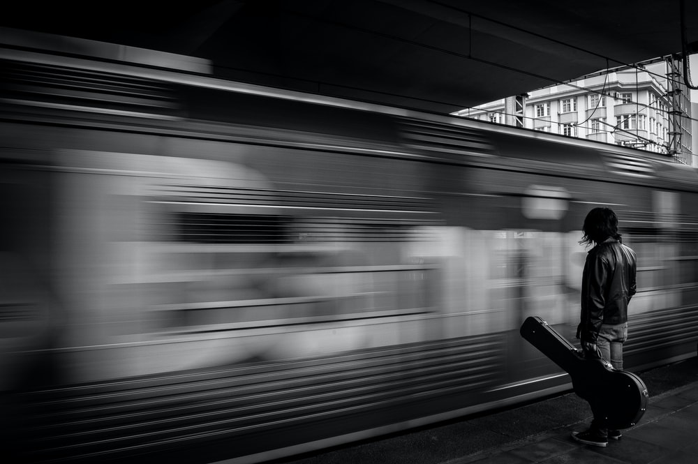grayscale photography of man holding guitar case standing infront of train