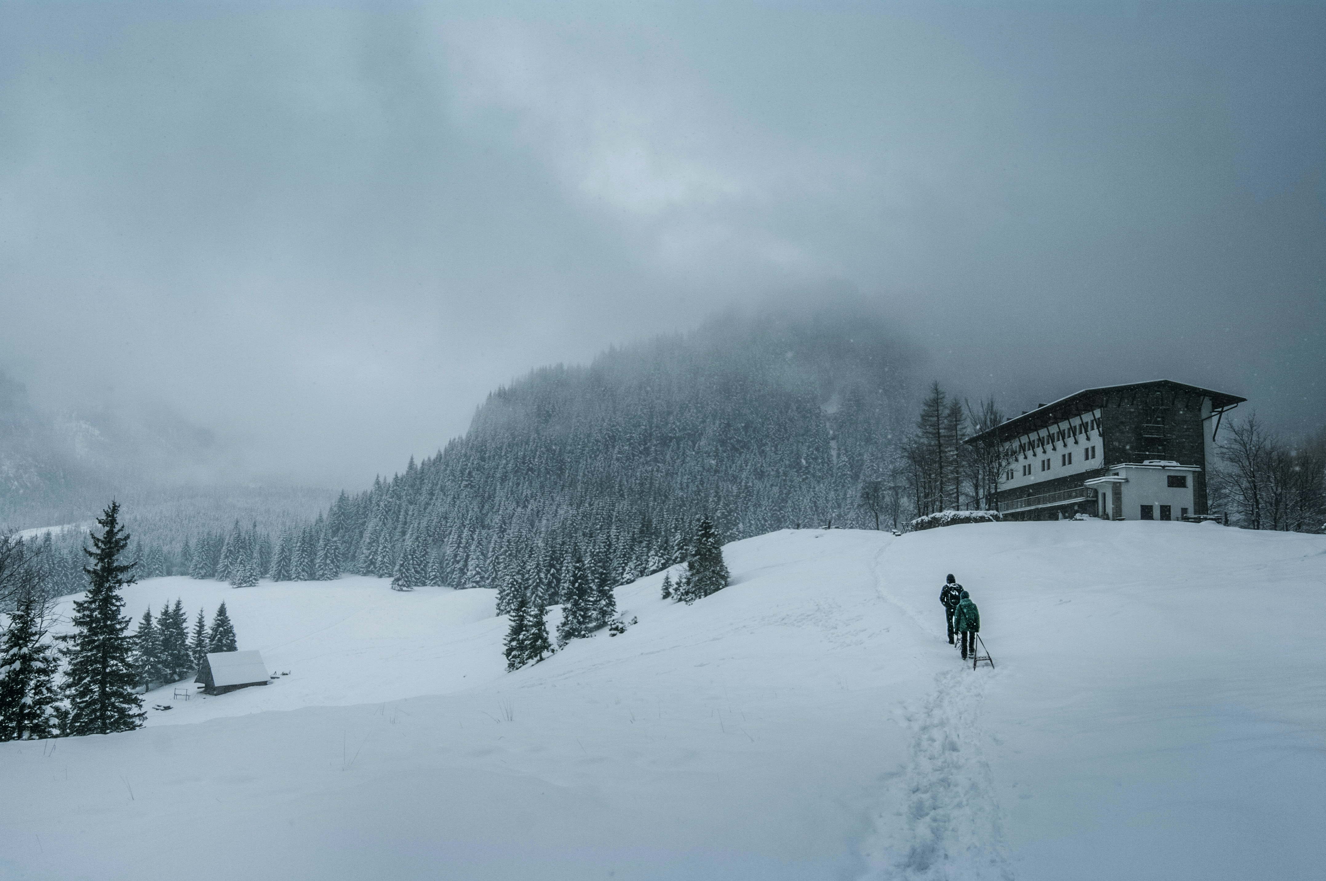 two persons walking on snow near concrete house under nimbus clouds
