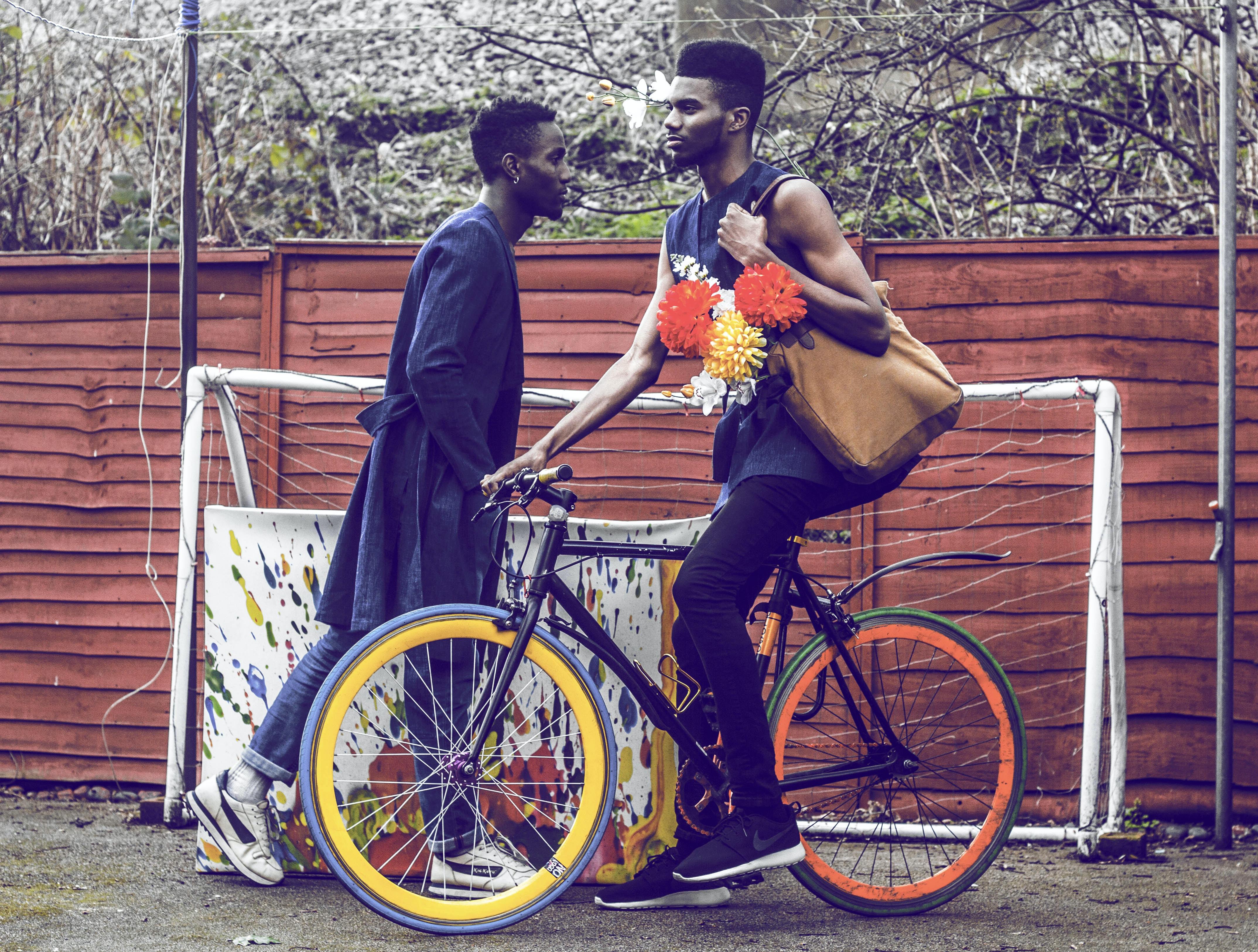 man holding brown bag riding bicycle