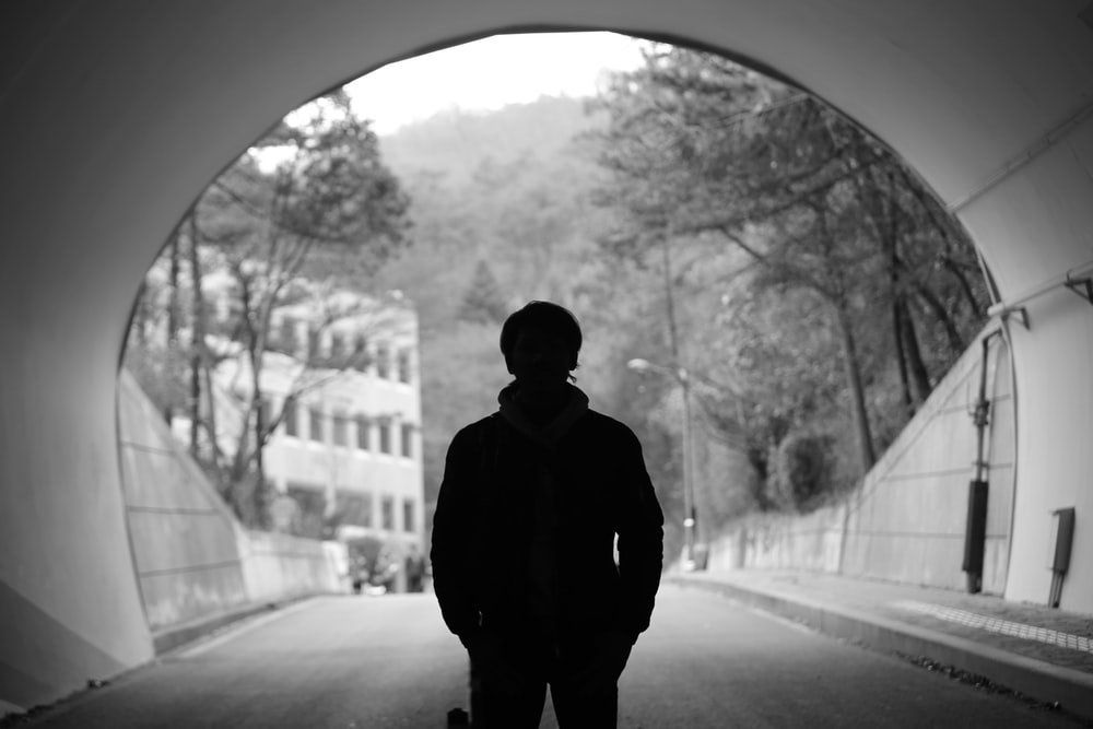 grayscale photography of man standing in tunnel