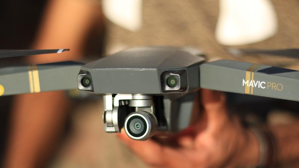 person holding gray DJI Mavic Pro drone