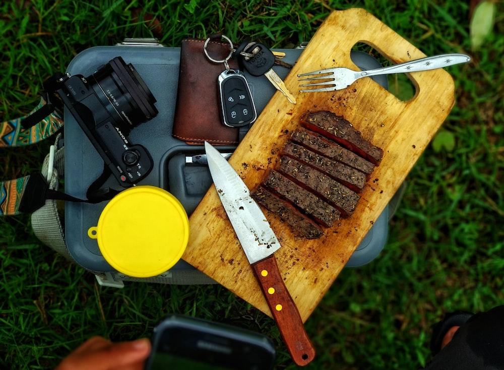 sliced meat on brown chopping board beside black DSLR camera
