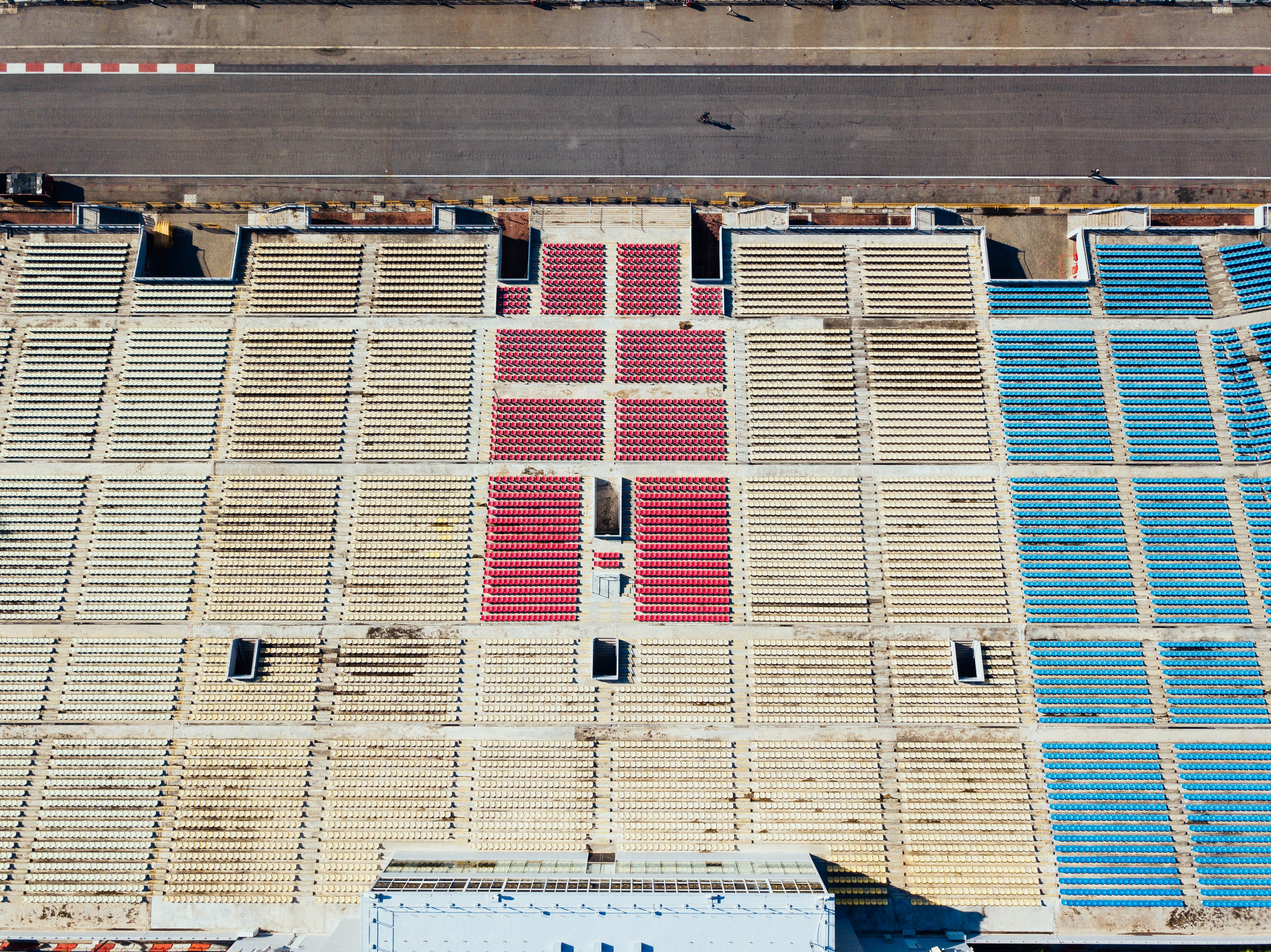 aerial photography of white, red, and blue chairs near black concrete race track