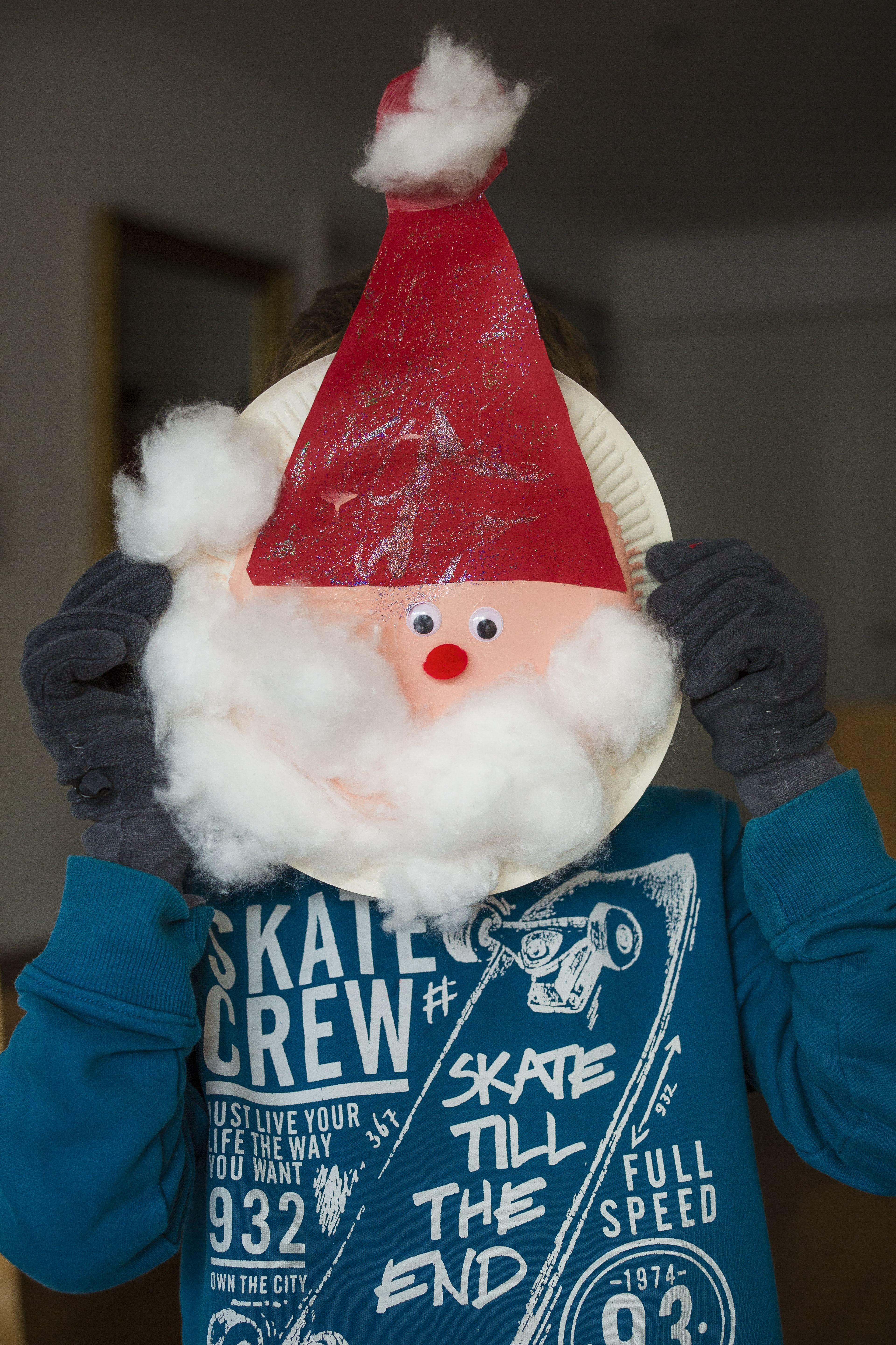 person holding white paper plate with Santa head inside room