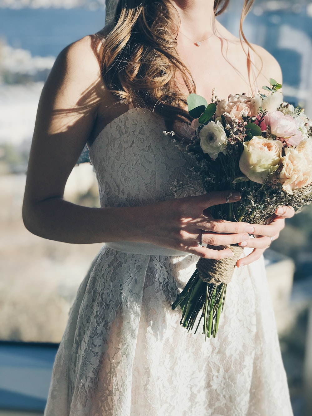 woman in white floral strapless dress holding flowers