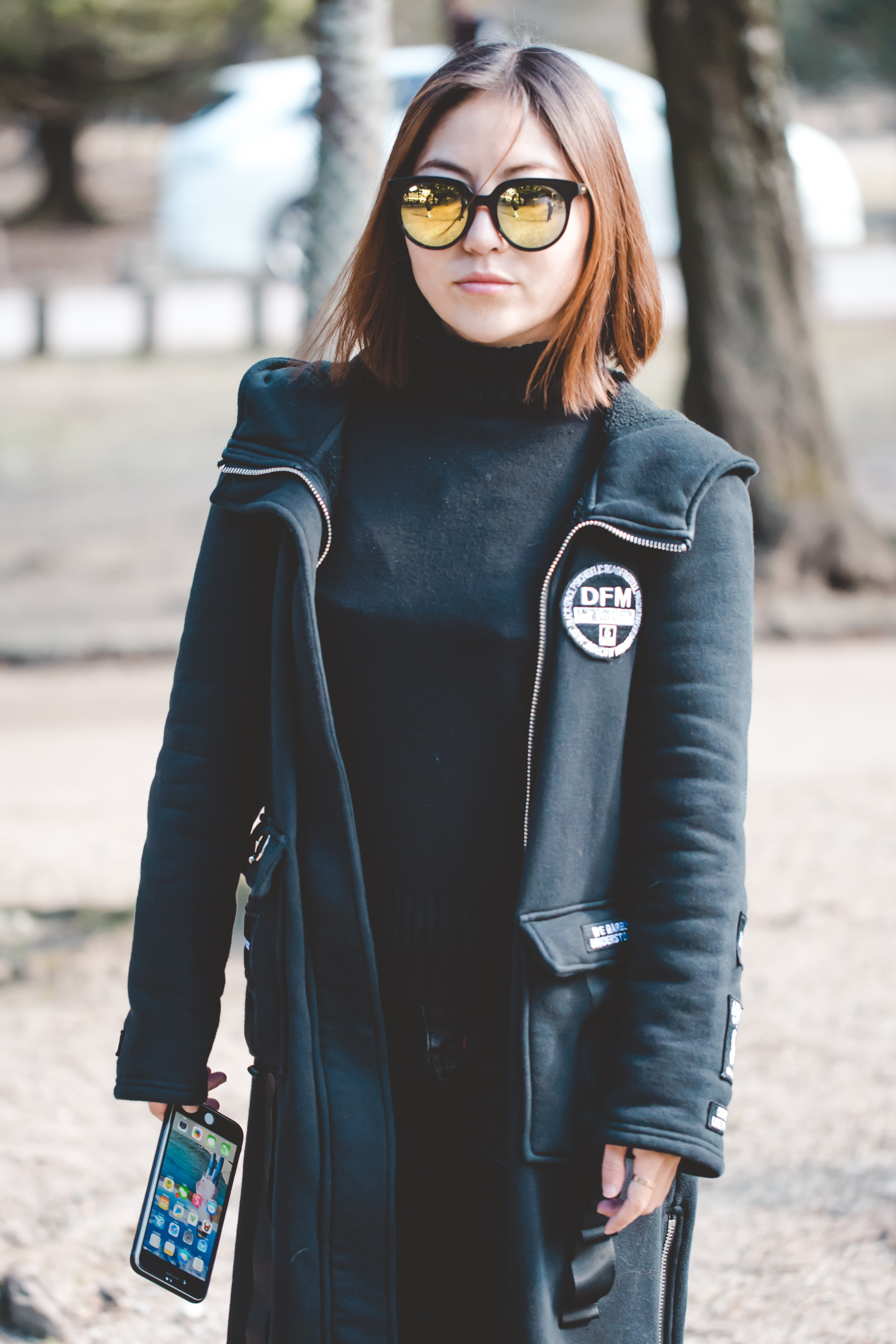 woman wearing sunglasses holding black Android smartphone