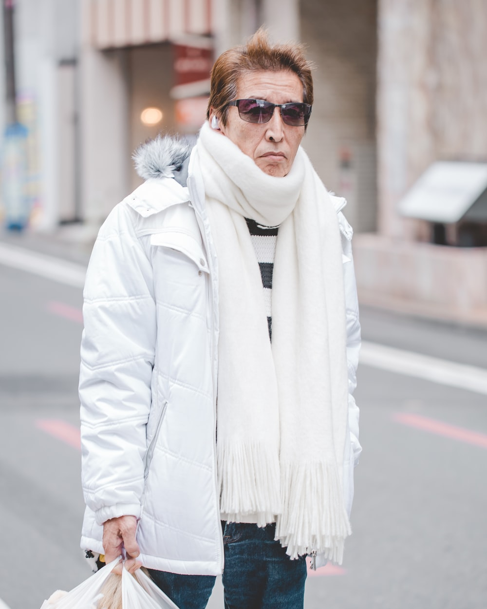 man in white parka jacket and white scarf walking on street at daytime
