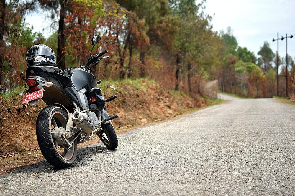 black full-face helmet on black naked motorcycle
