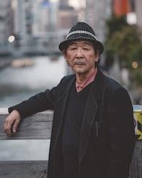man wearing black hat standing against wooden handrail