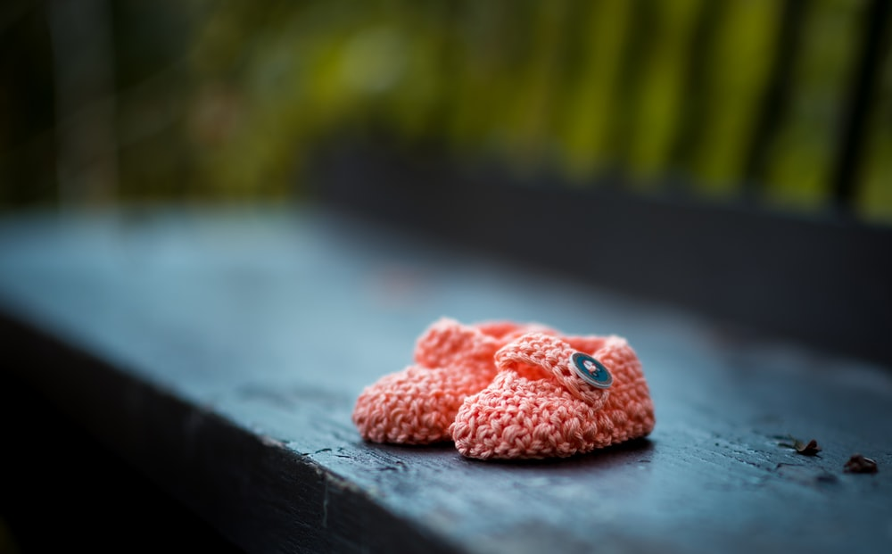 pair of baby's pink knit shoes on bench - support local Winnipeg Metropolitan Region