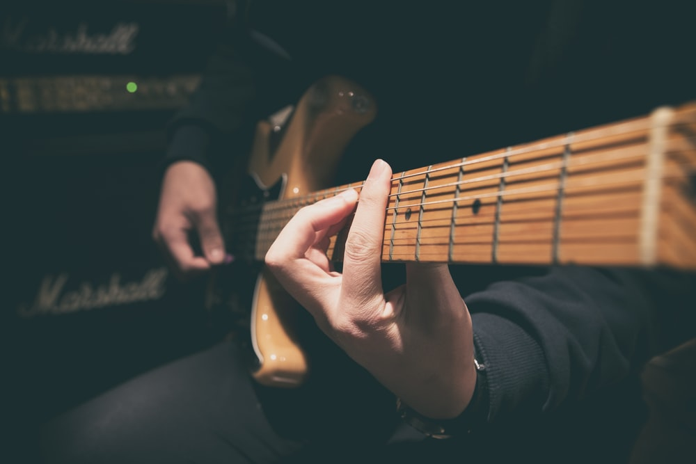 person wearing black shirt paying guitar in closeup photography