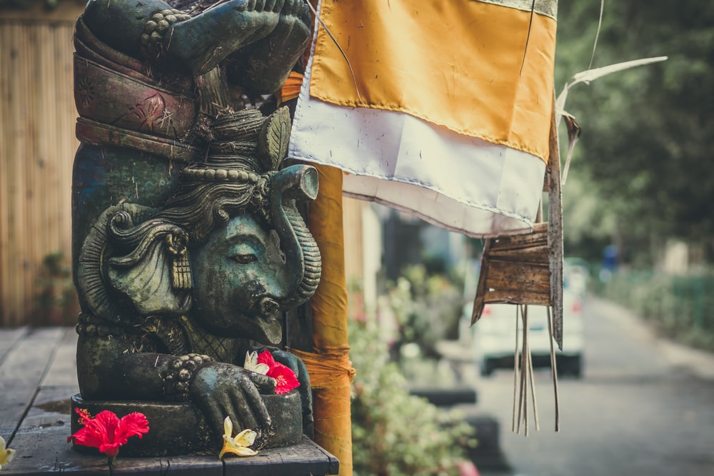 Ganesha statuette beside a flag