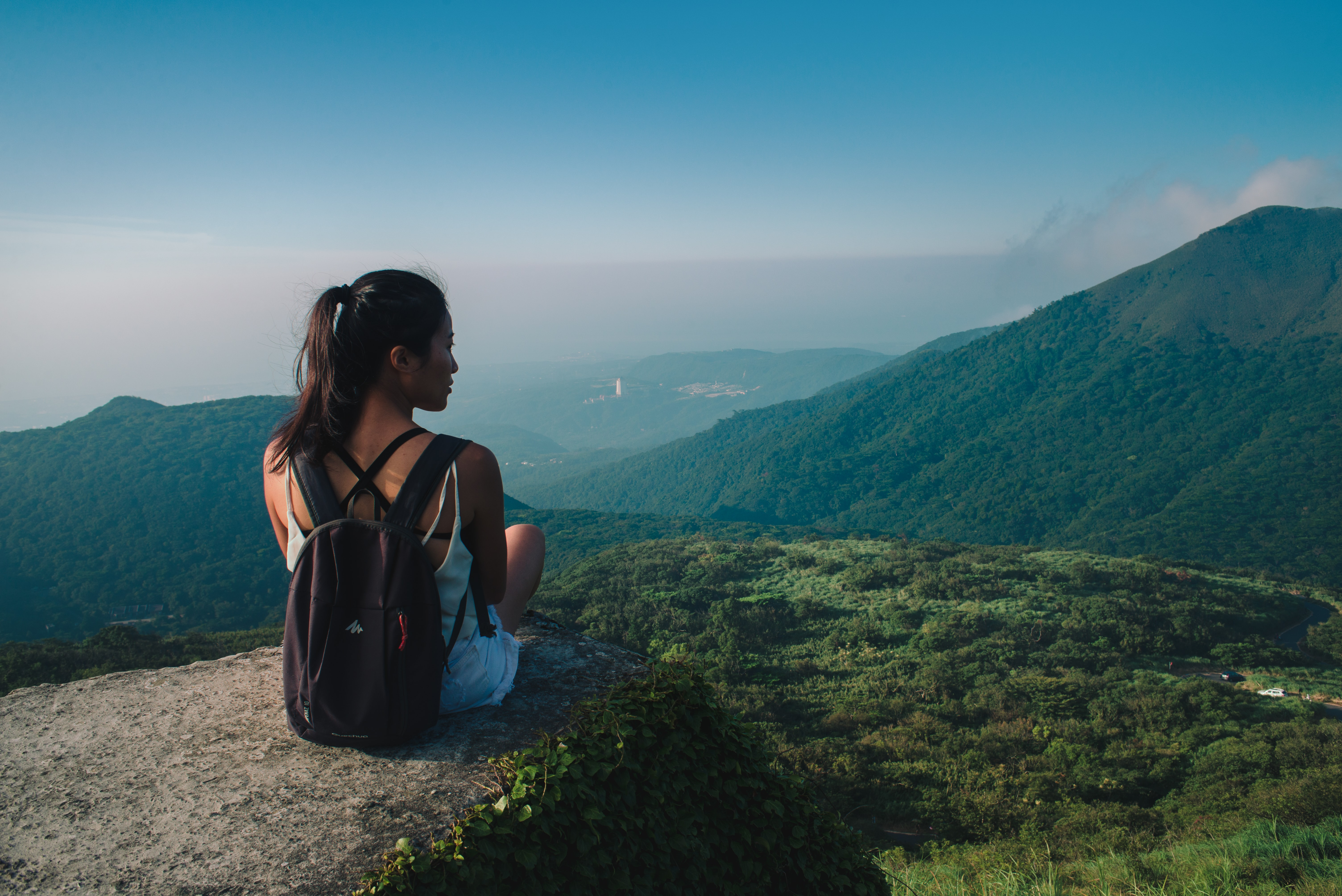 woman carrying black backpack sitting on top of hill