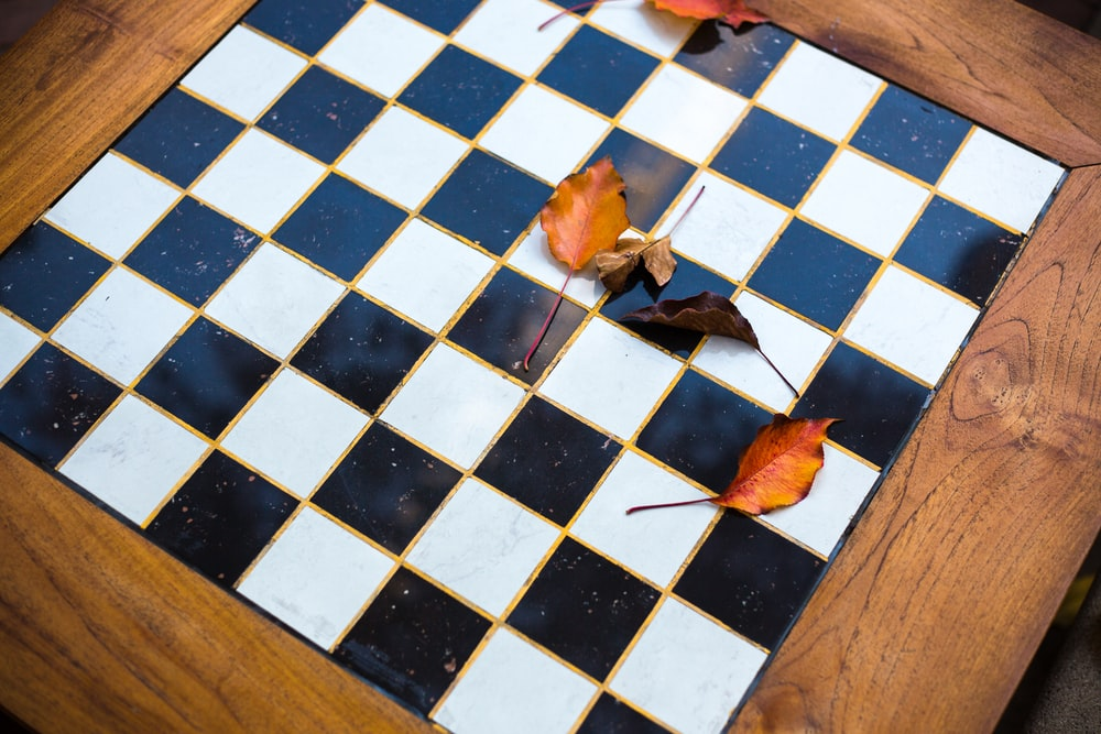 blue and white marble top, brown wooden framed chessboard containing dried leaves