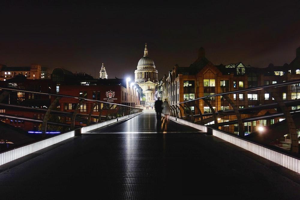 two people walking on bridge during nighttime