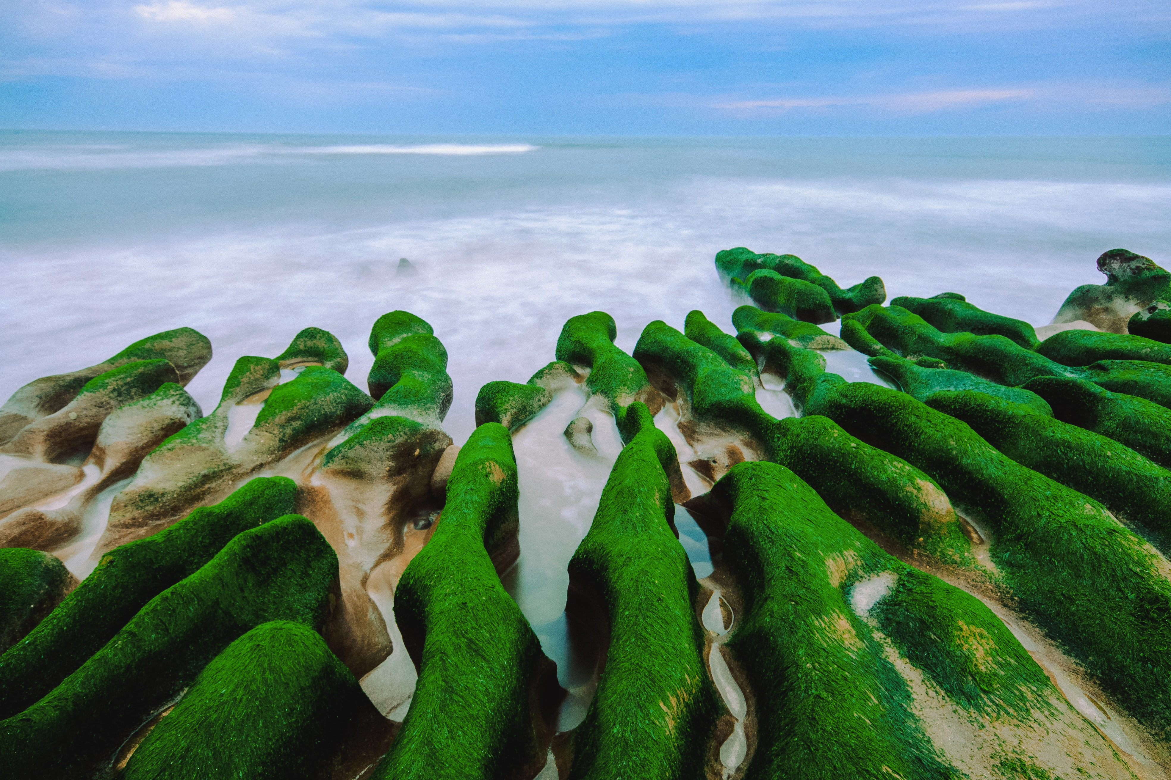 aerial photography of moss-covered stone formation at shore at daytime