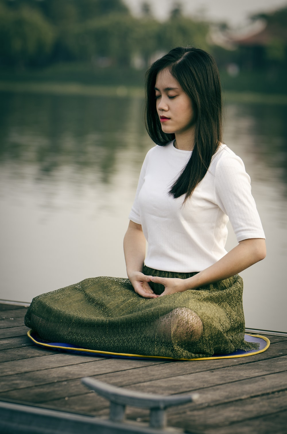 woman meditating on wooden dock during daytime