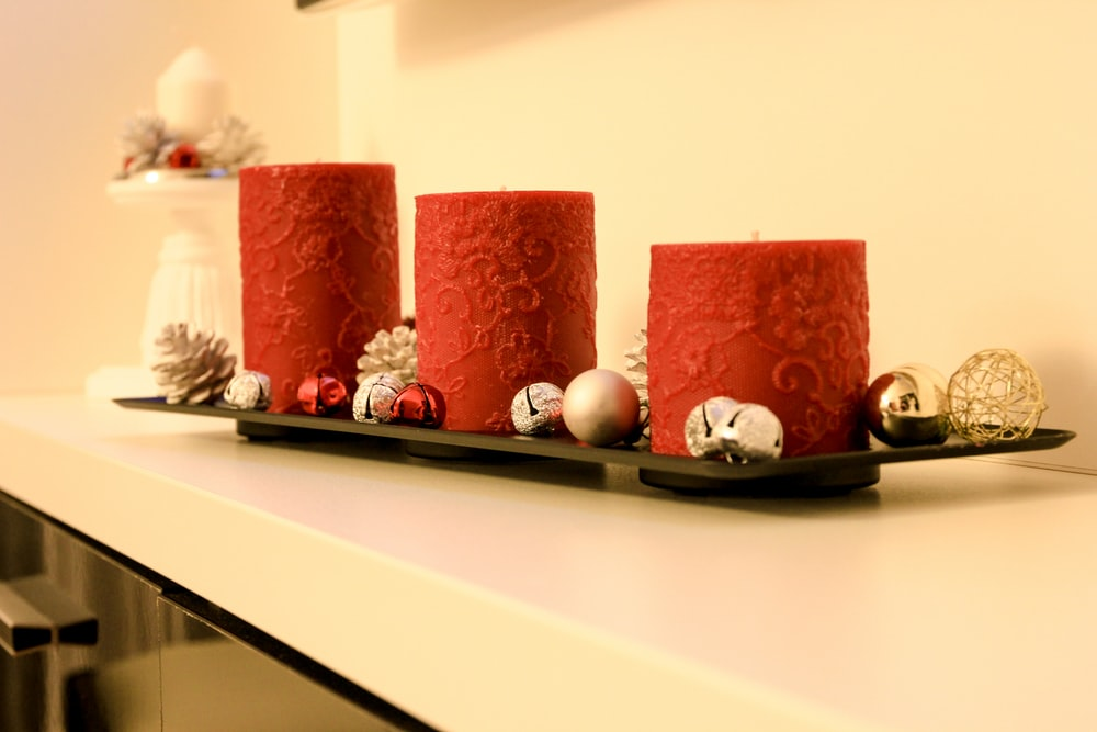 three red pillar candles on black holder