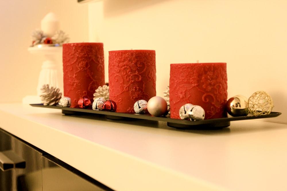 three red pillar candles on black holder