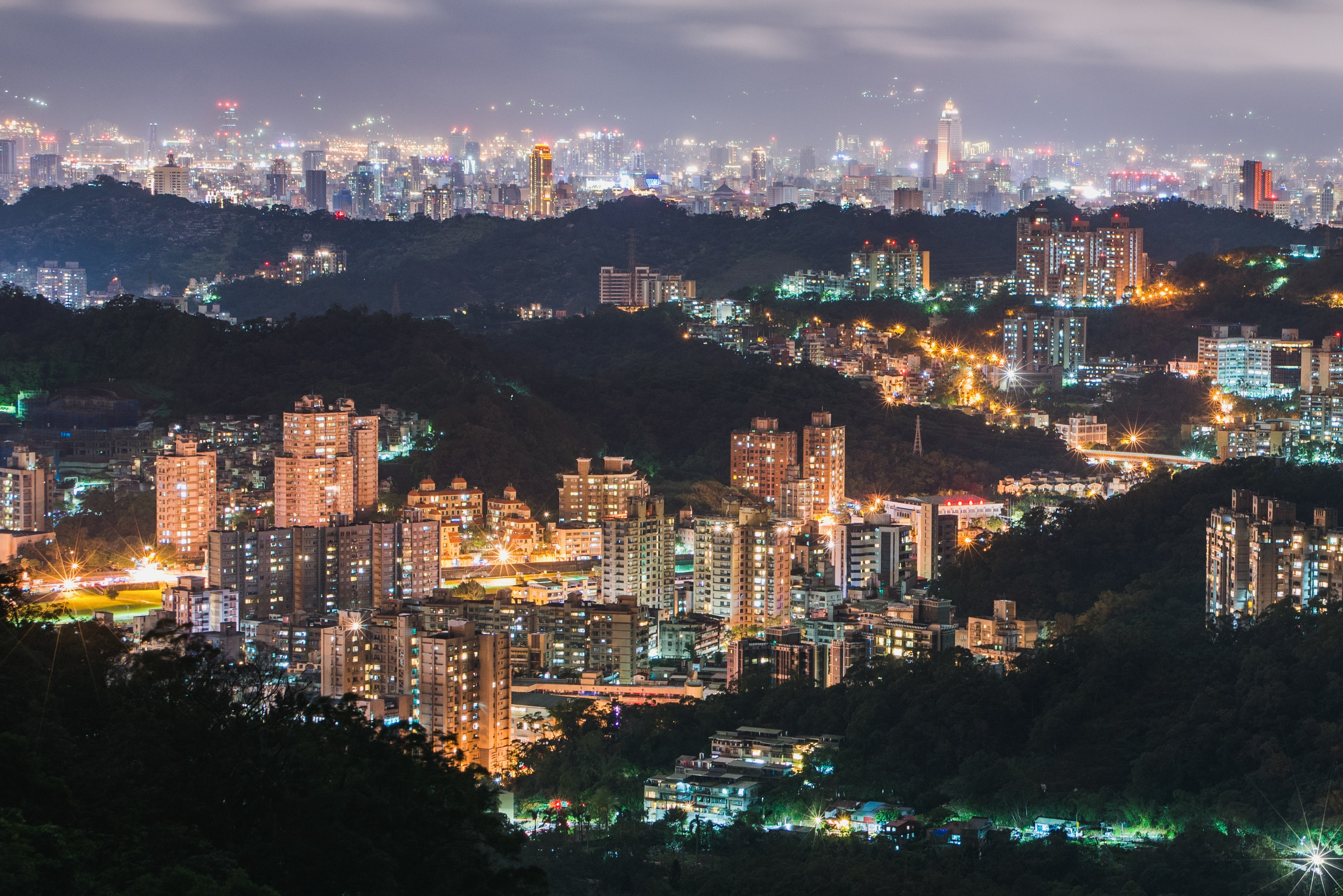 aerial view of hills and high-rise buildings with lights