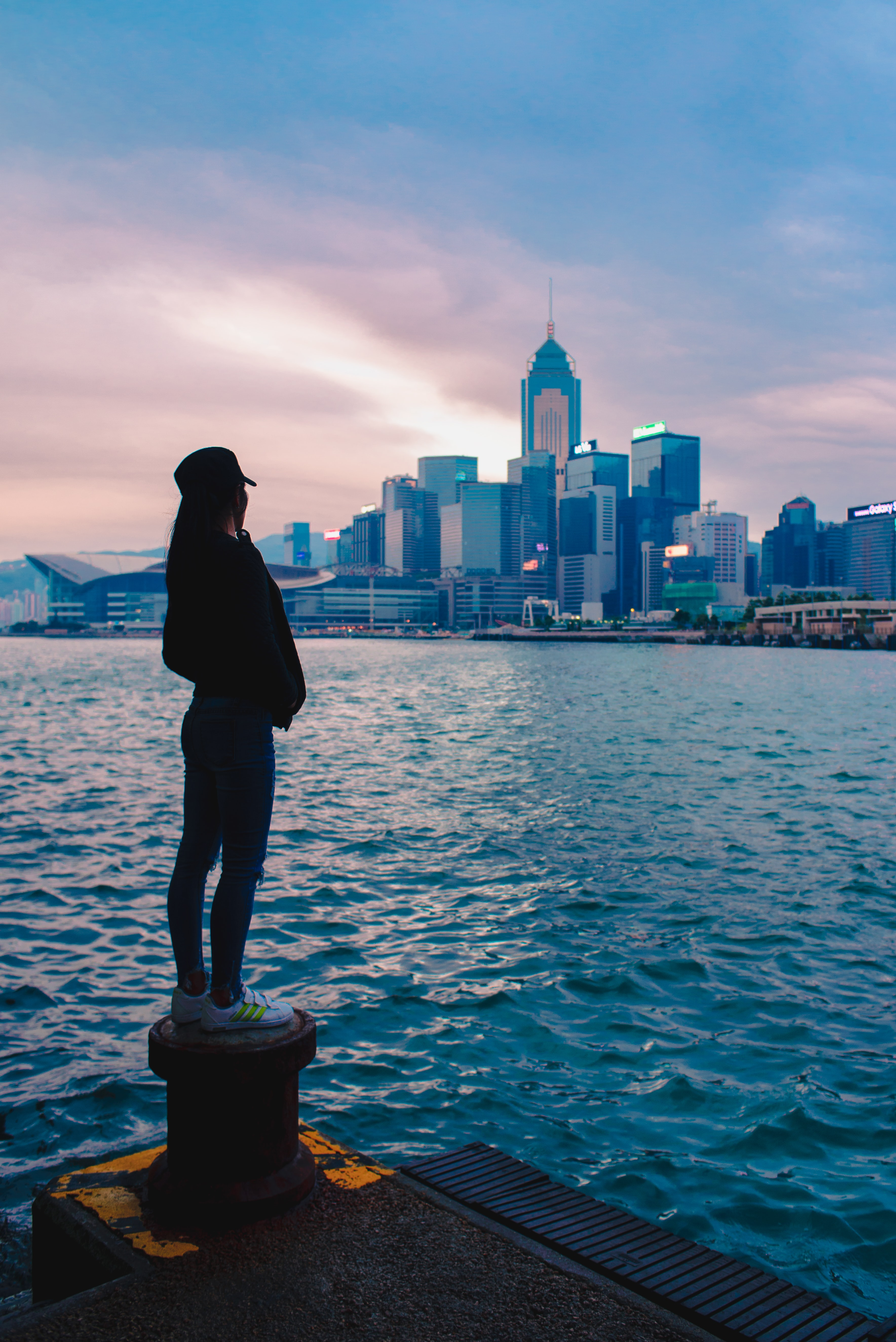 woman in black jacket standing on spool beside body of water with overlooking view of buildings under dark clouds background