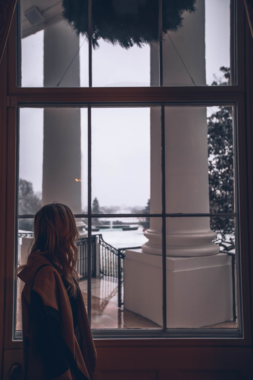 woman standing in front of window inside room