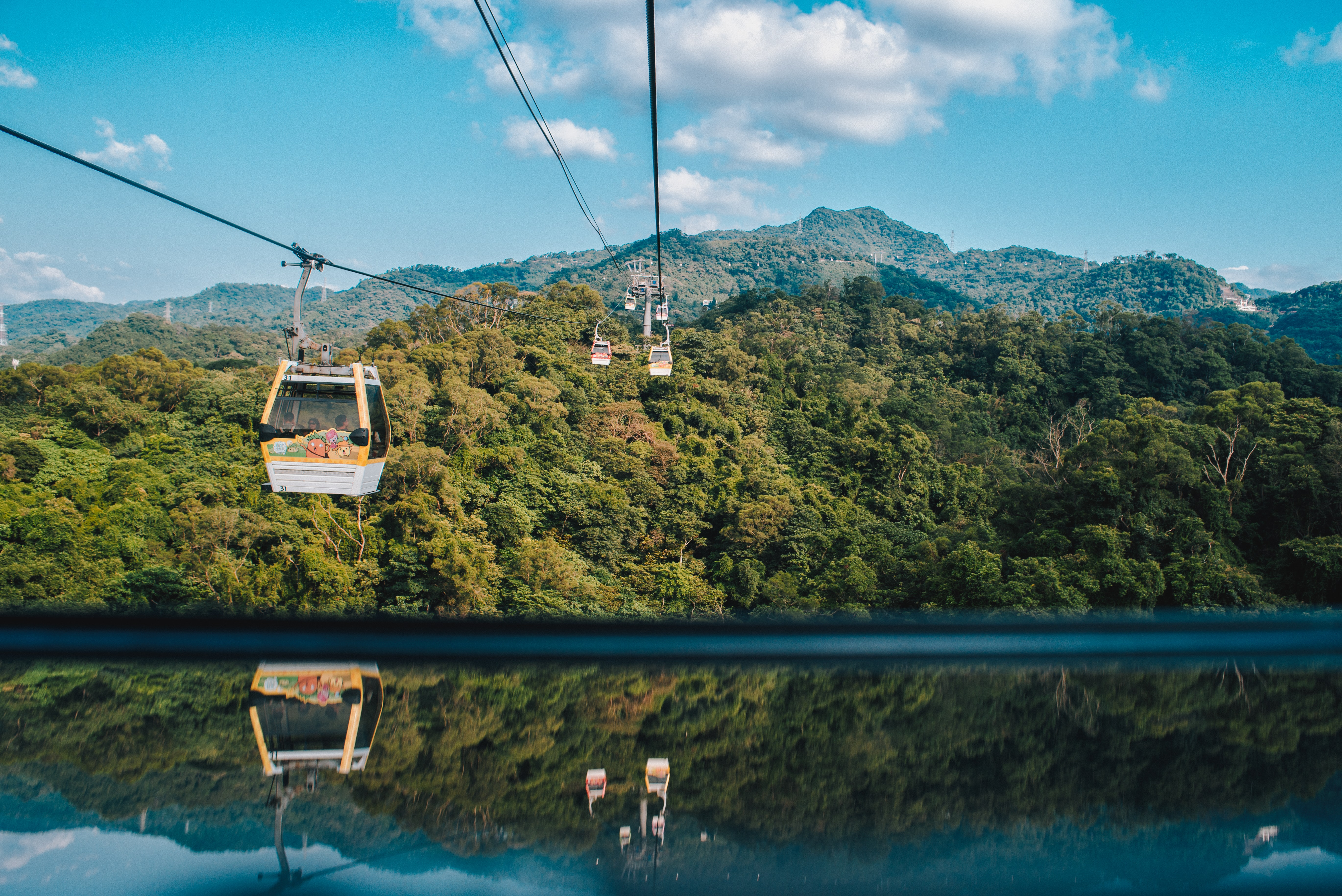 white and orange cable car above body of water