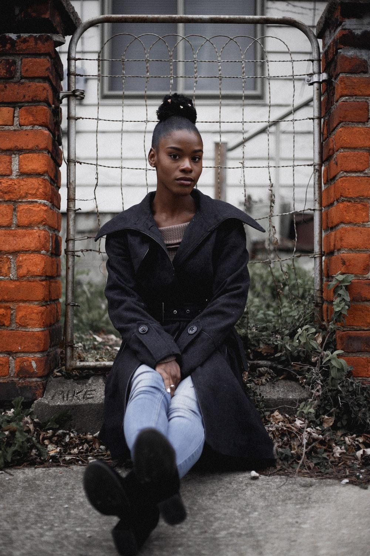 woman sitting near grey gate