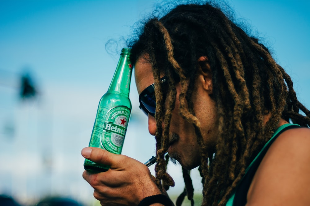 person holding Heineken beer bottle