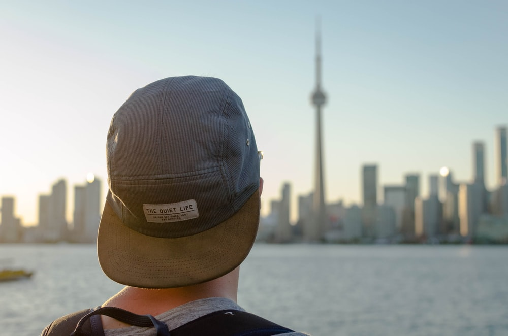 person wearing gray hat facing on city during daytime photography