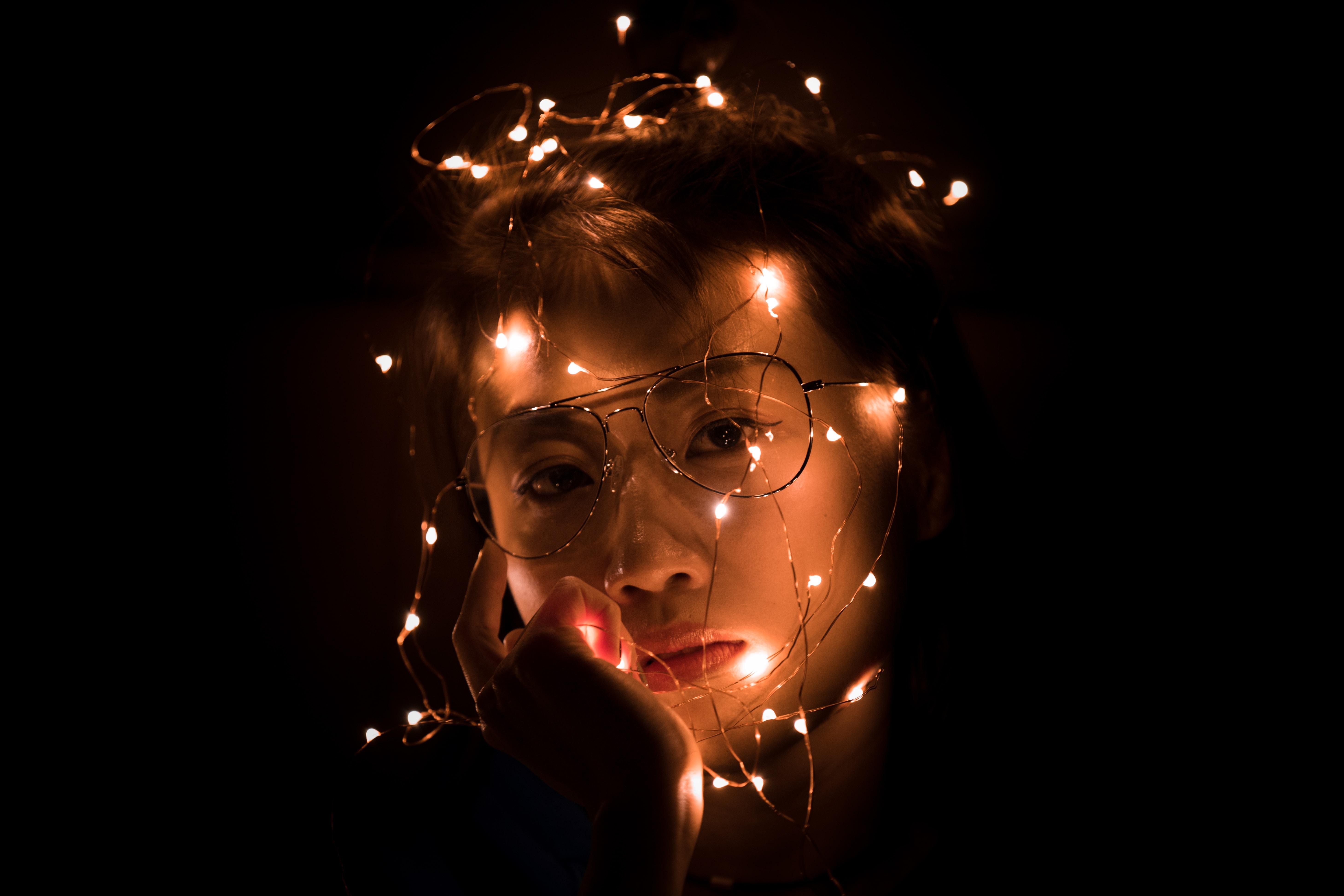 string light portrait photography of woman wearing eyeglasses