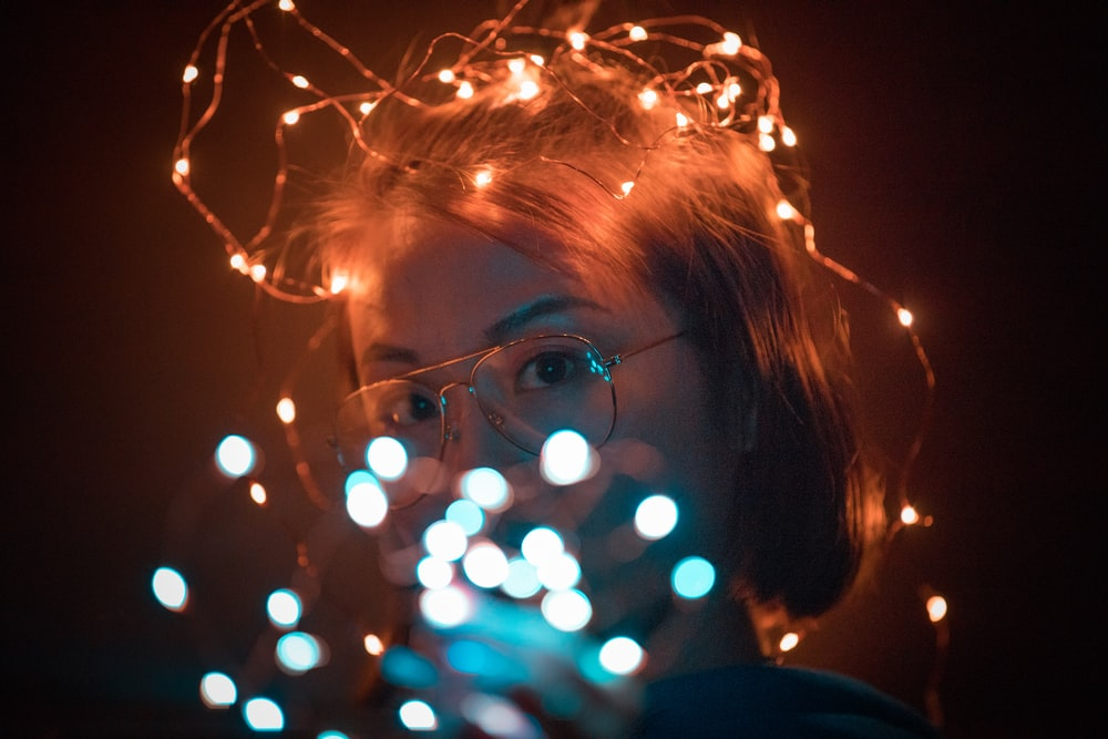 woman wearing brown framed eyeglasses with string lights on her head