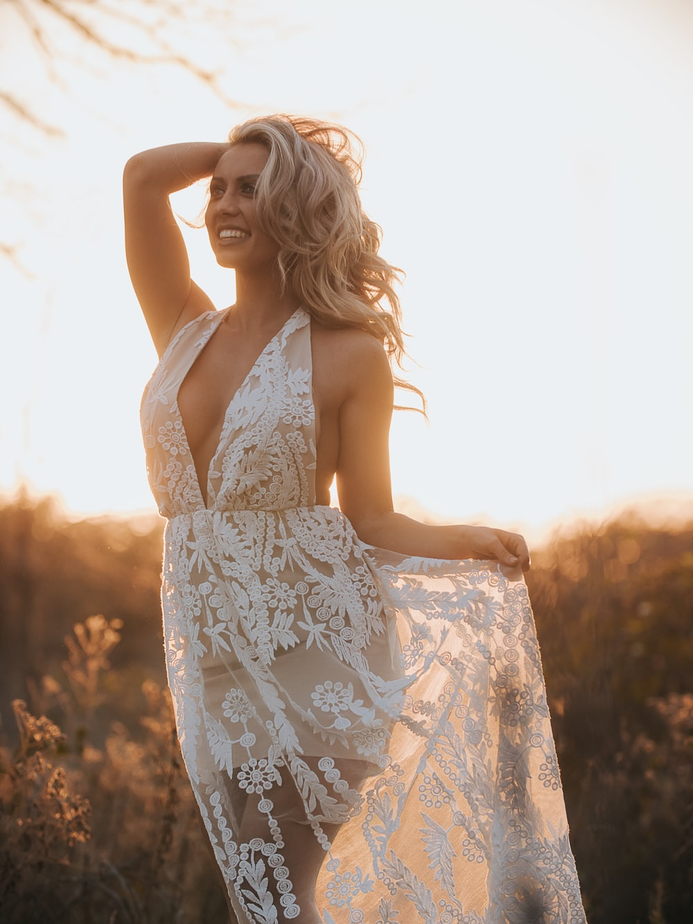 woman holding her dress and head near grass during golden hour