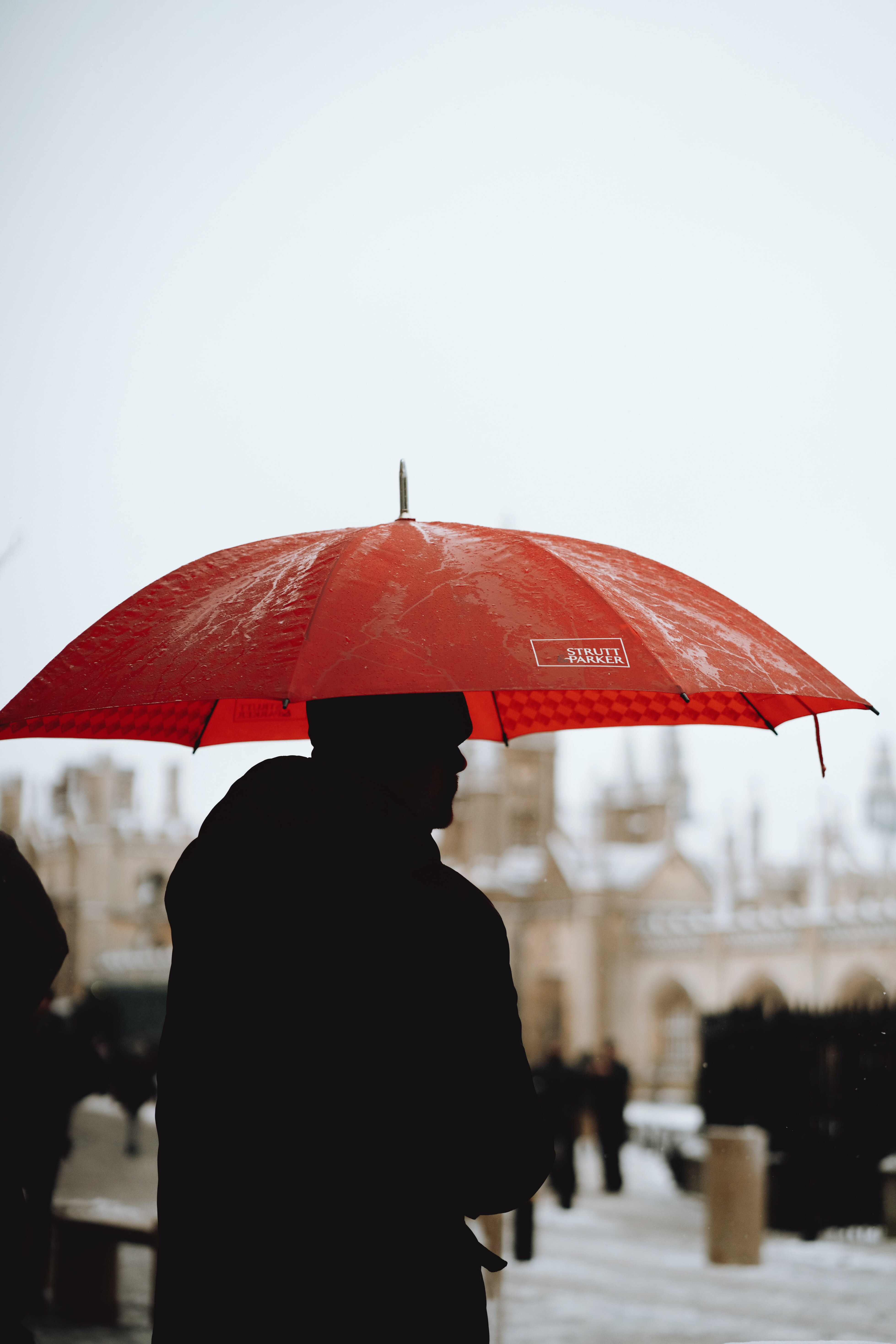 silhouette of person using umbrella at daytime photography