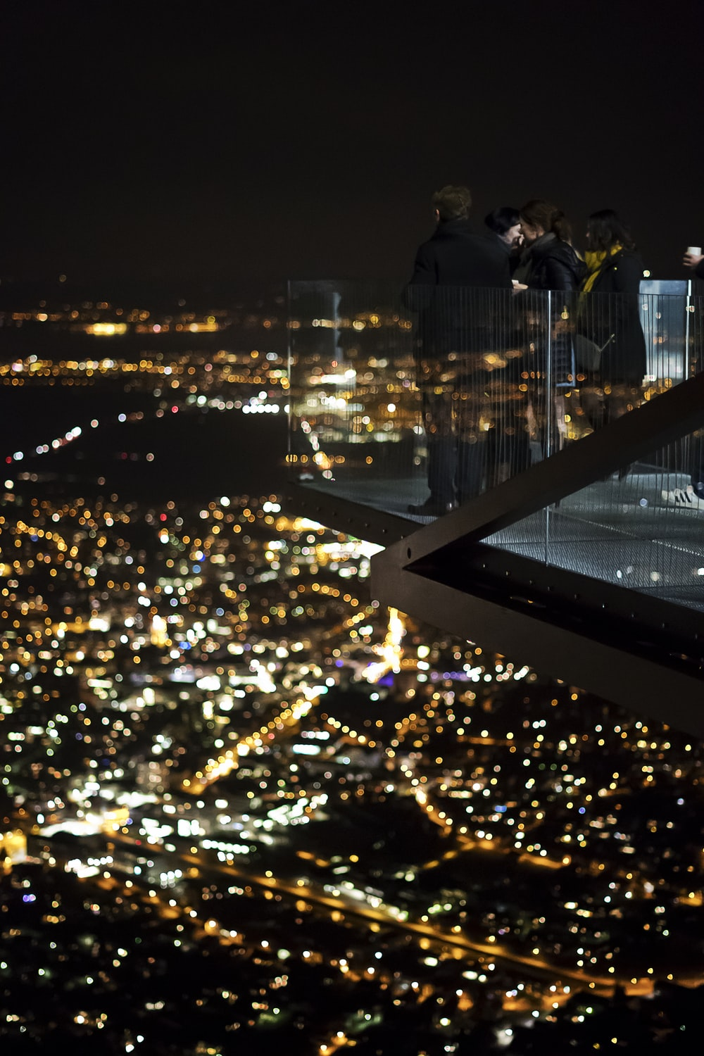 several people on glass patio of a skyscraper during night