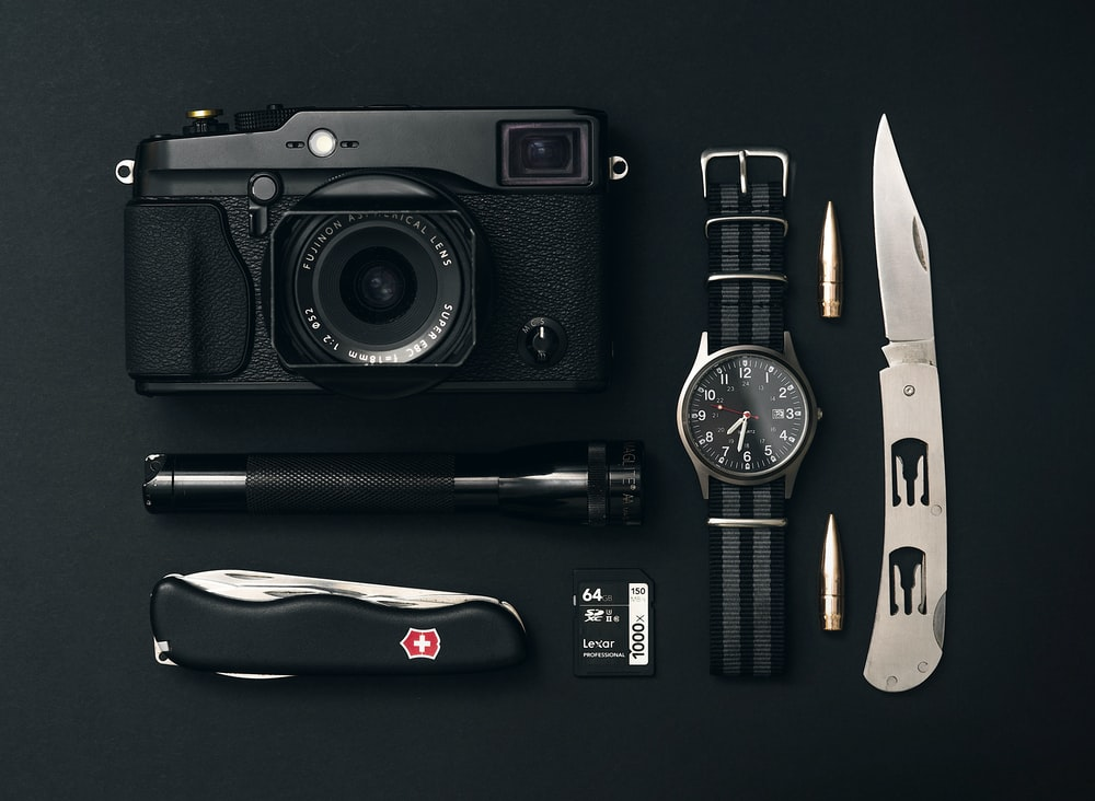 black camera, round silver-colored analog watch, black Swiss Gear pocketknife, and black flashlight