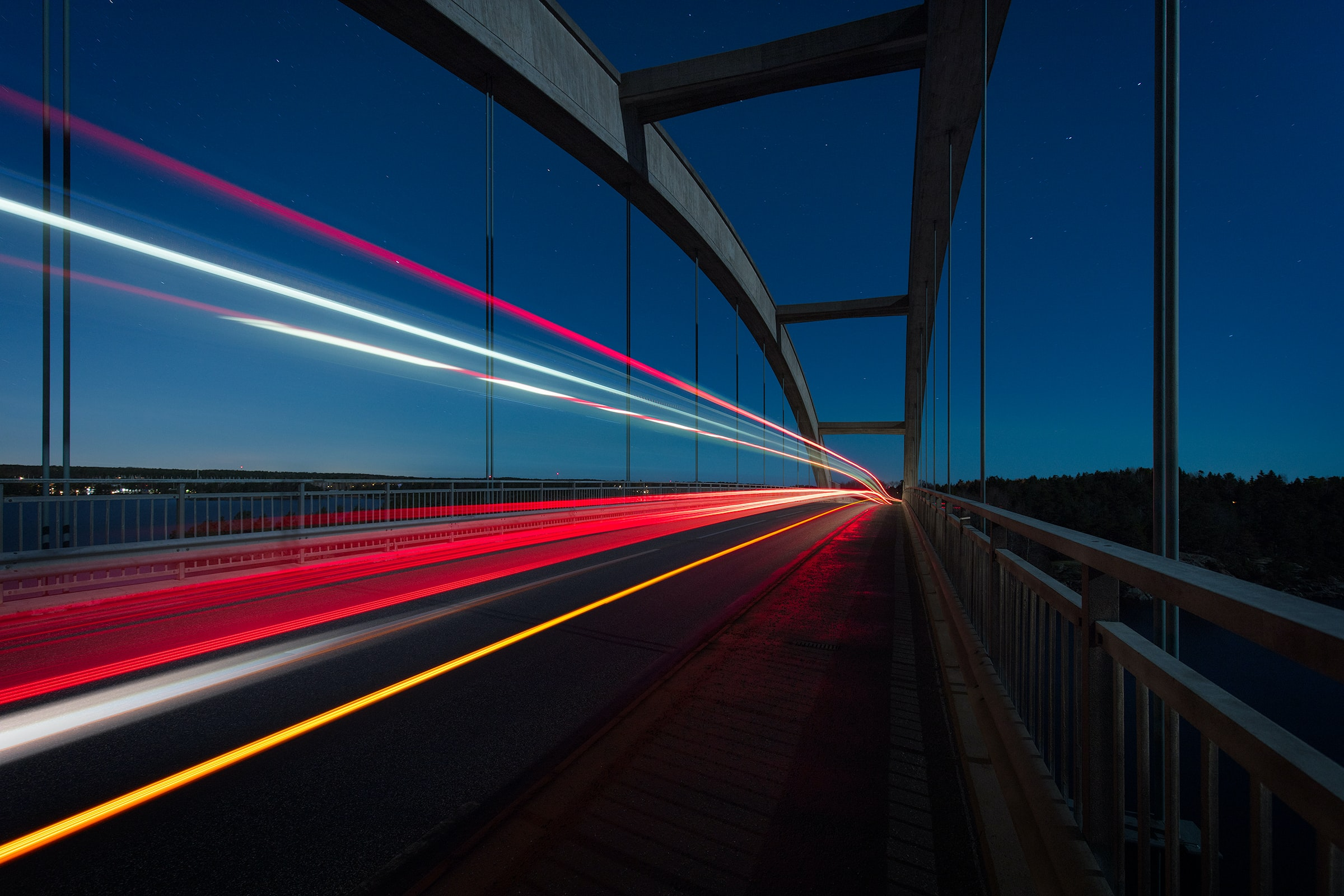 gray suspension bridge with streaks of light time lapse photography