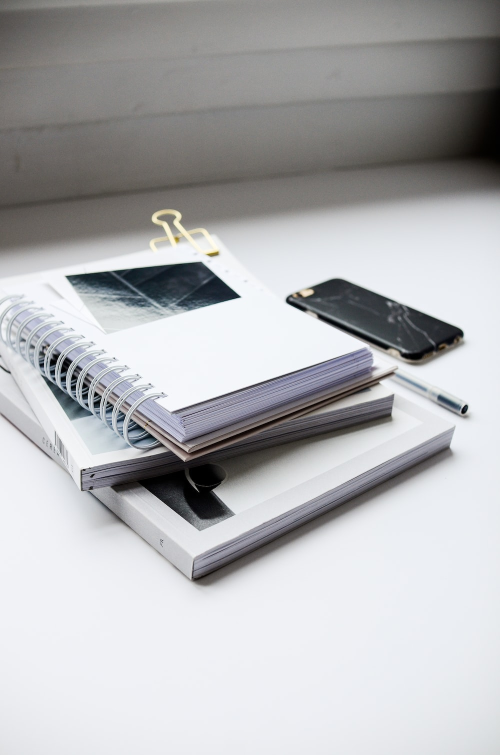 white spiral notebook beside black smartphone on white table