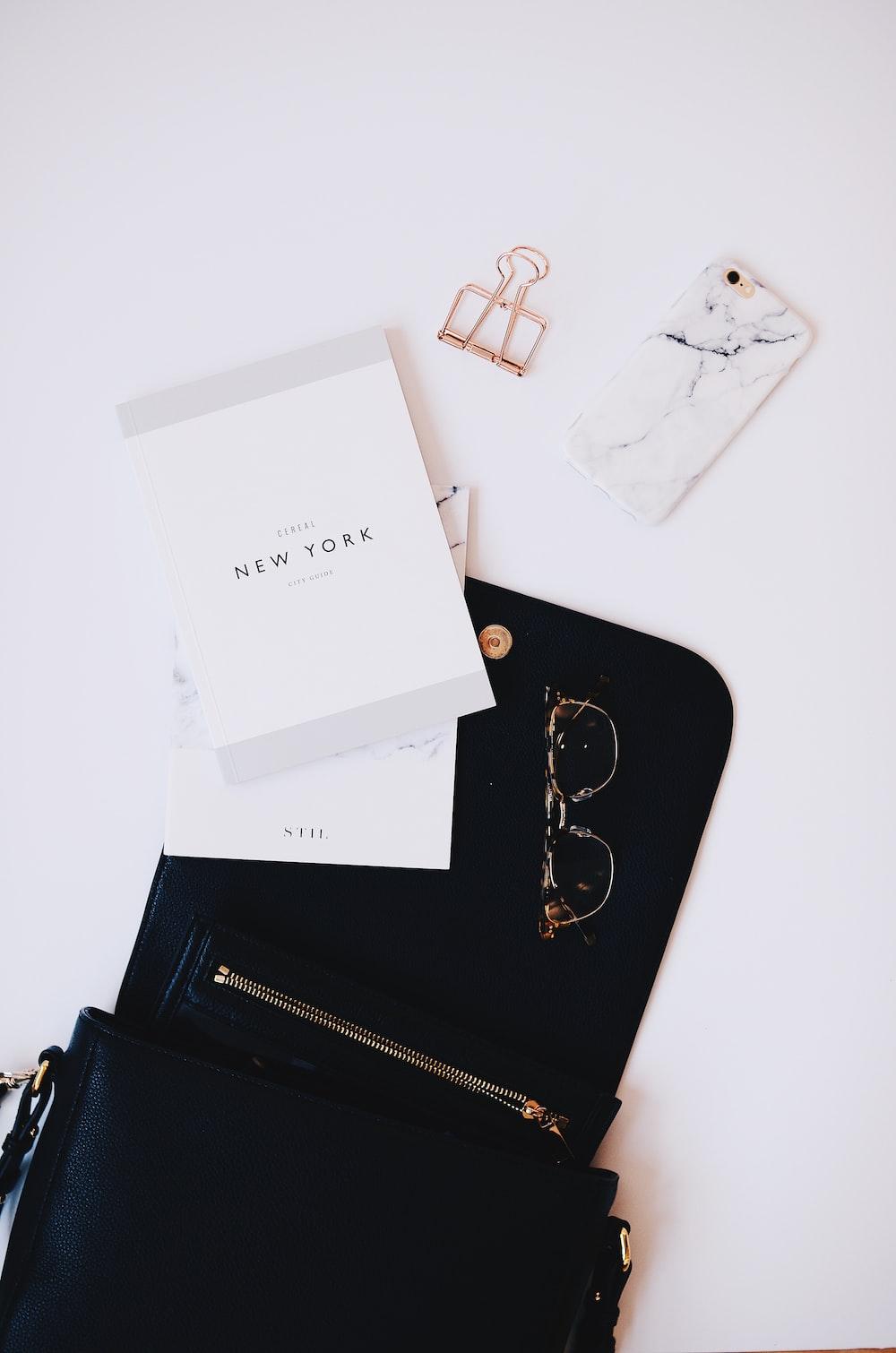 gold framed sunglasses, black phone case near gold clip