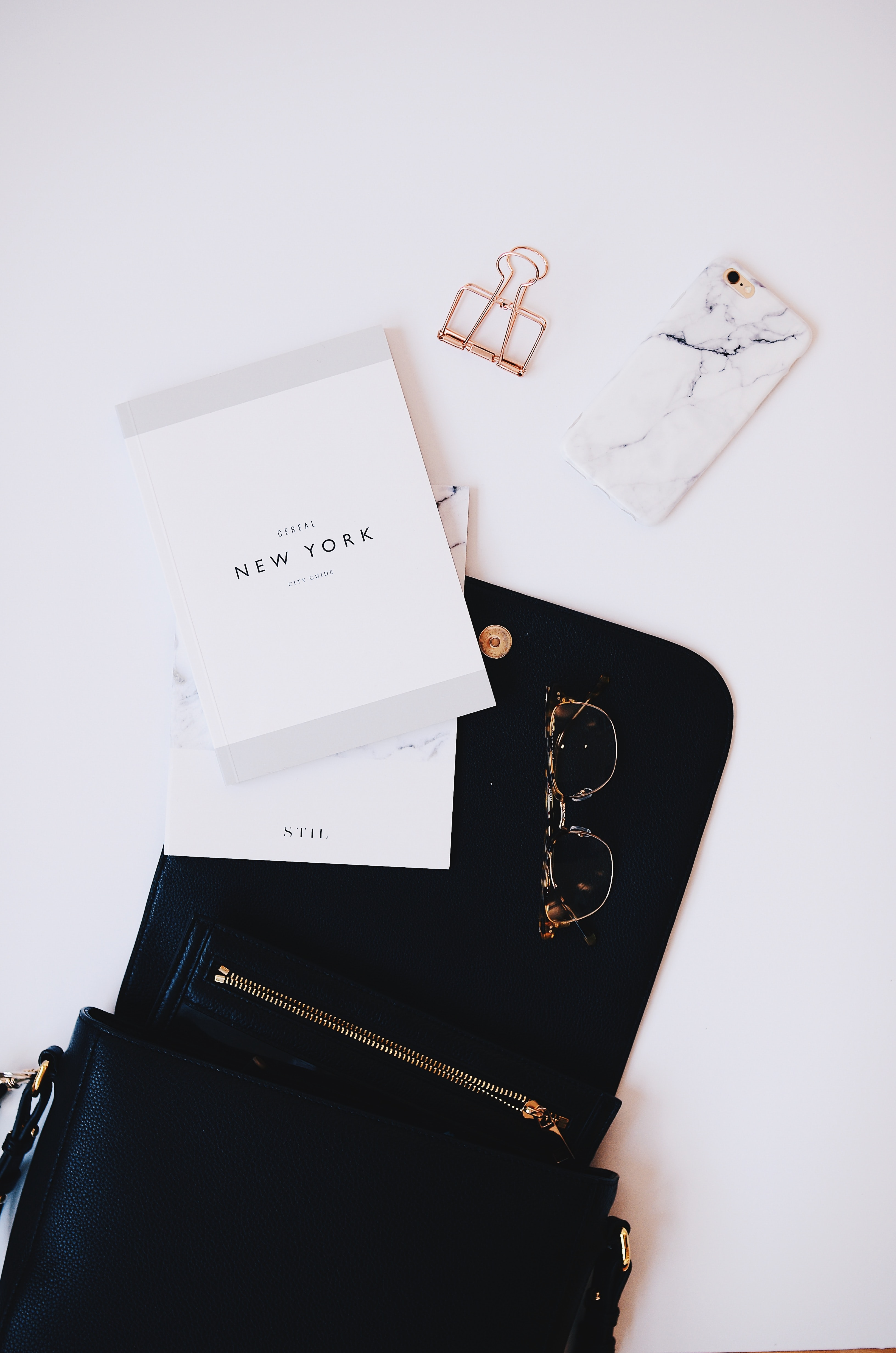 gold framed sunglasses, black phone case near gold clip