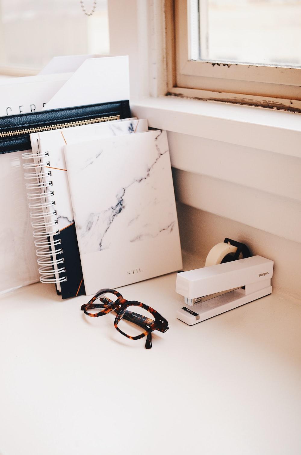 white stapler and eyeglasses with brown tortoiseshell frame on desk
