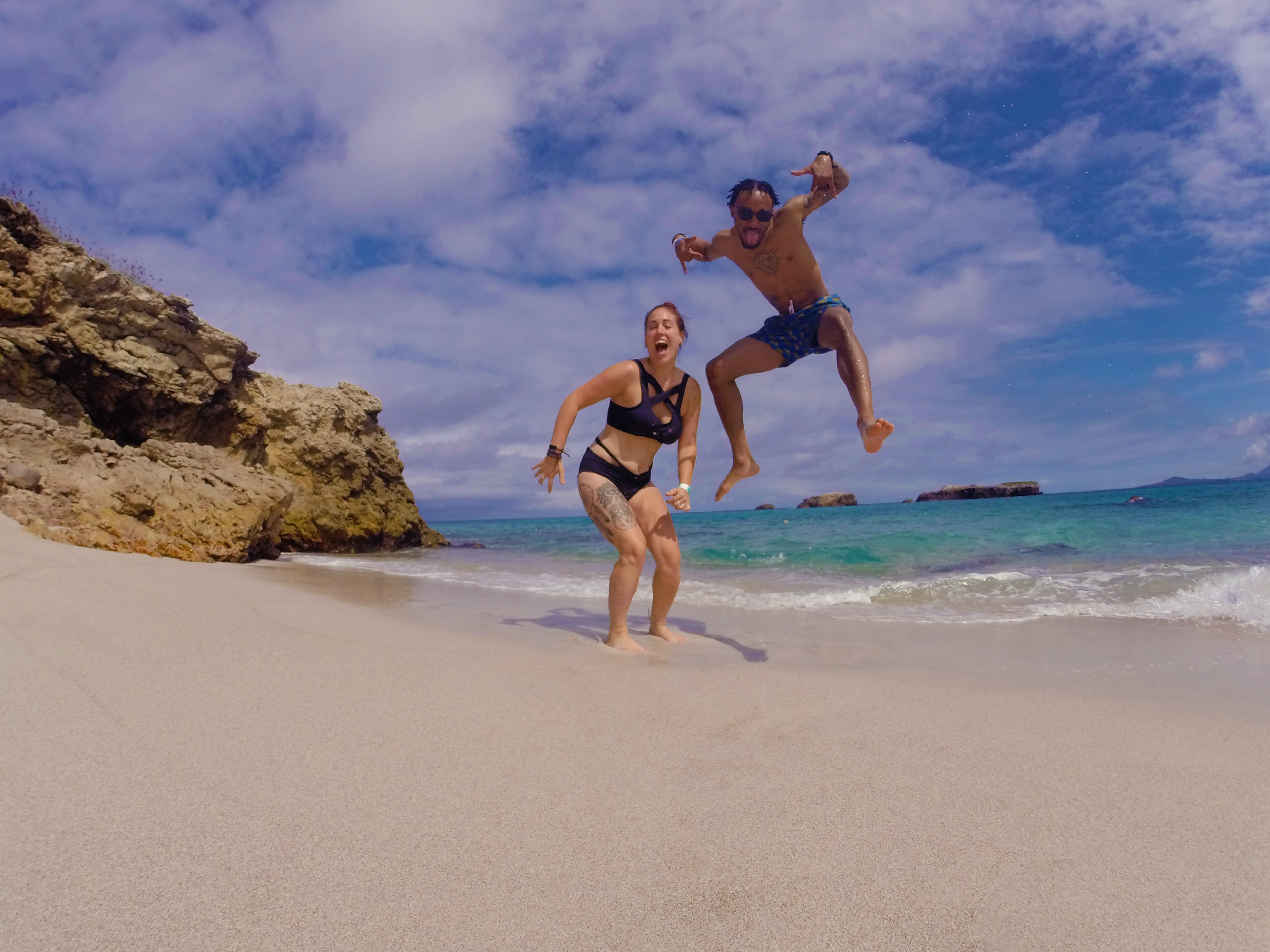 man and woman taking photo beside seashore during daytime
