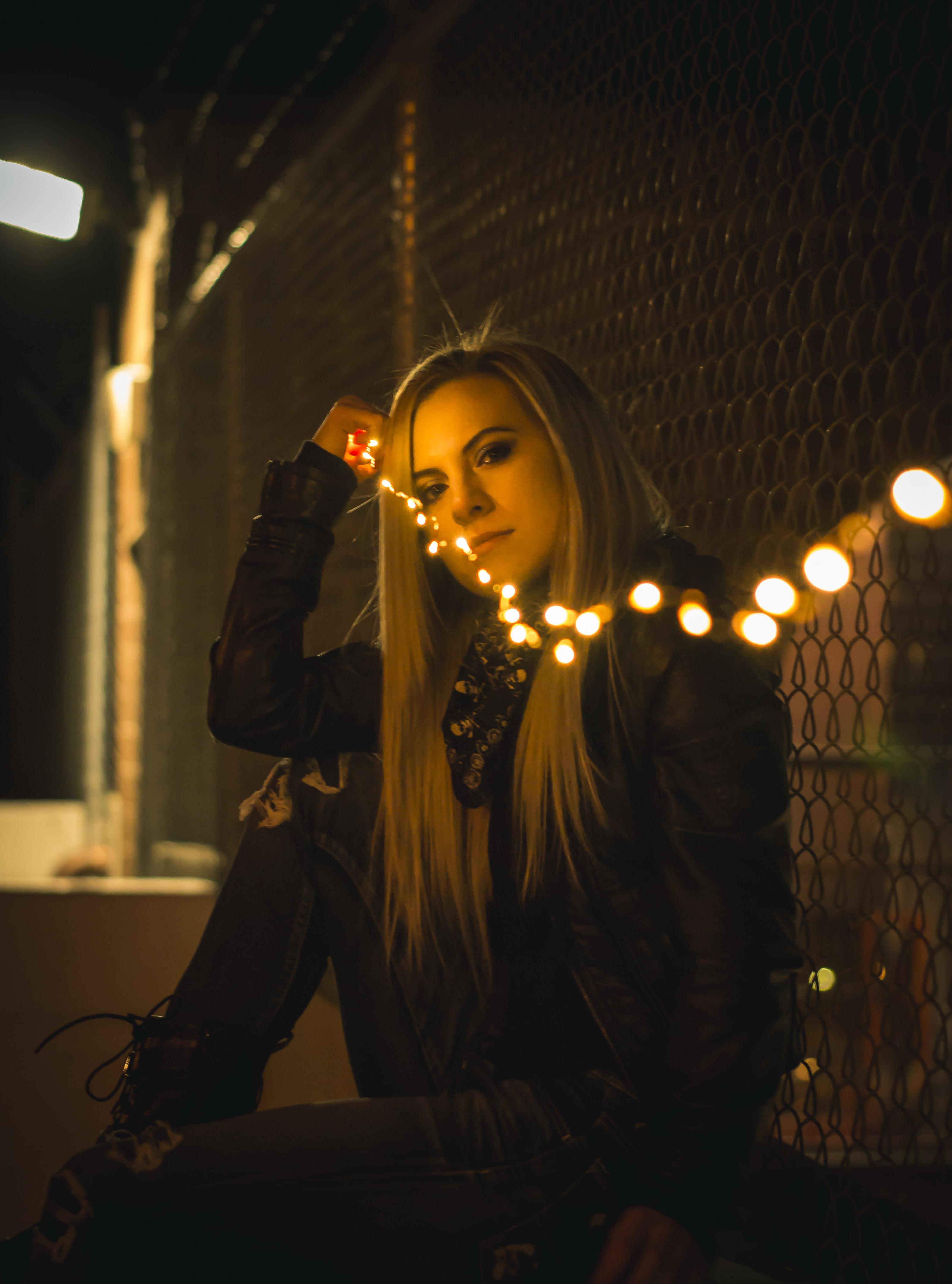 woman in black long-sleeved shirt holding string light