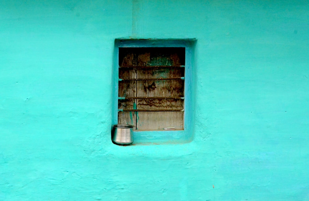 gray steel container on window with teal paint