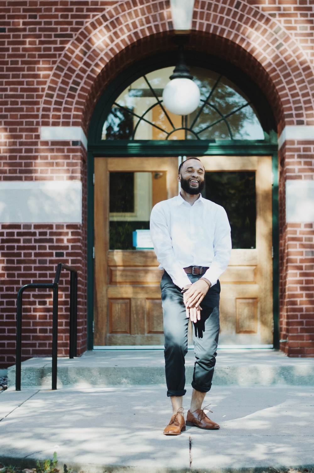man standing in front of brown wooden door during daytime