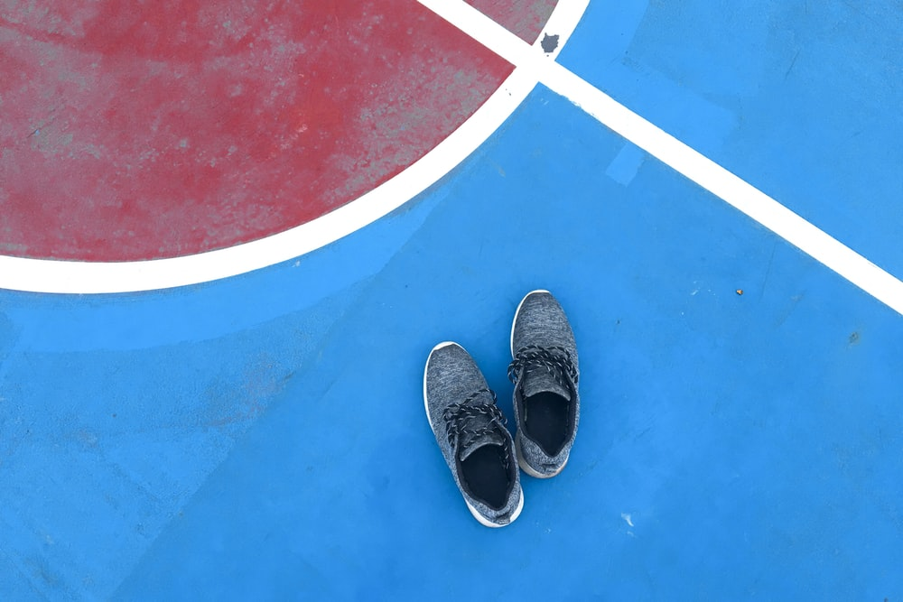 pair of blue shoes on ball court