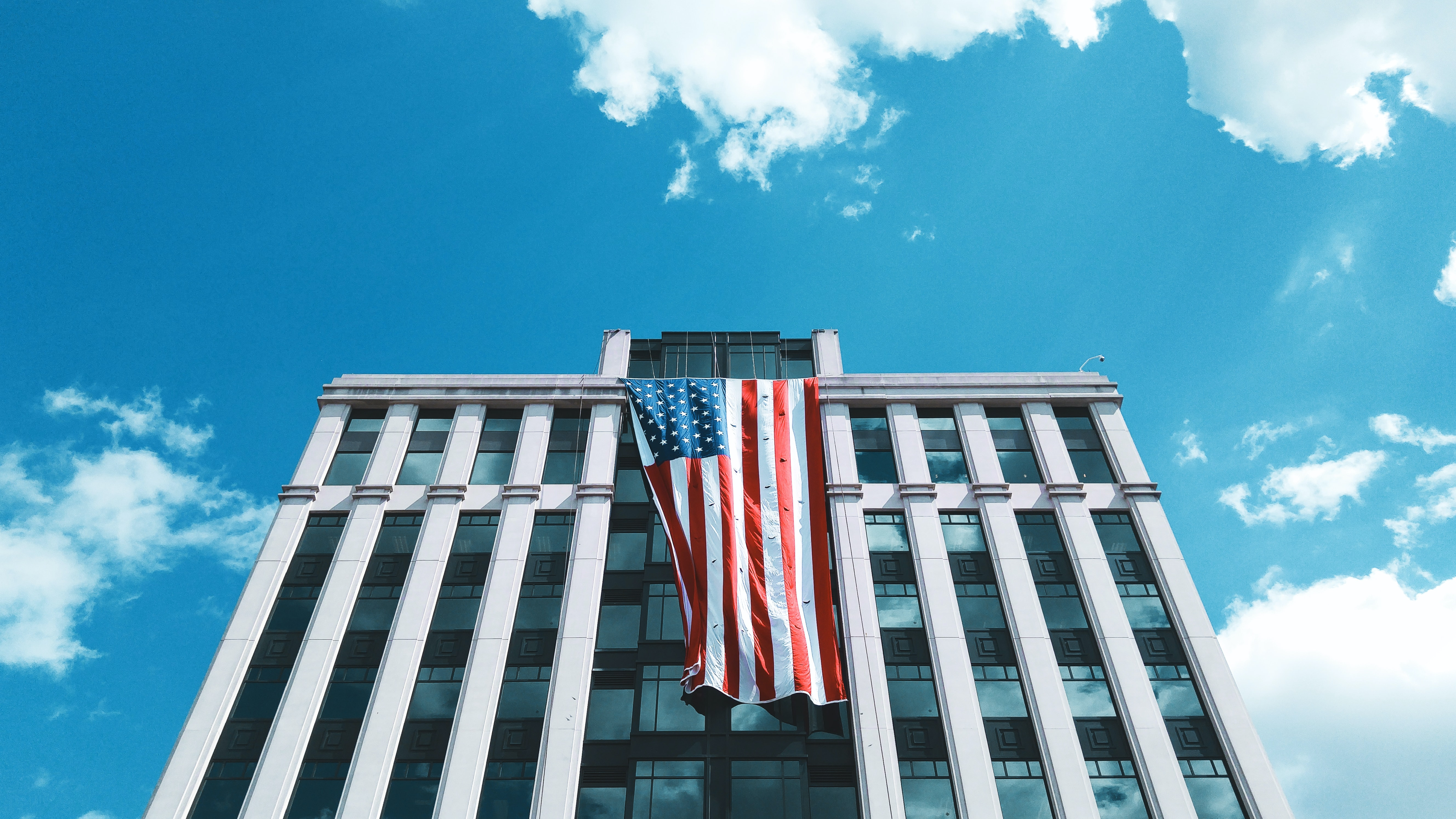 low-angle photography of gray concrete building with flag of USA
