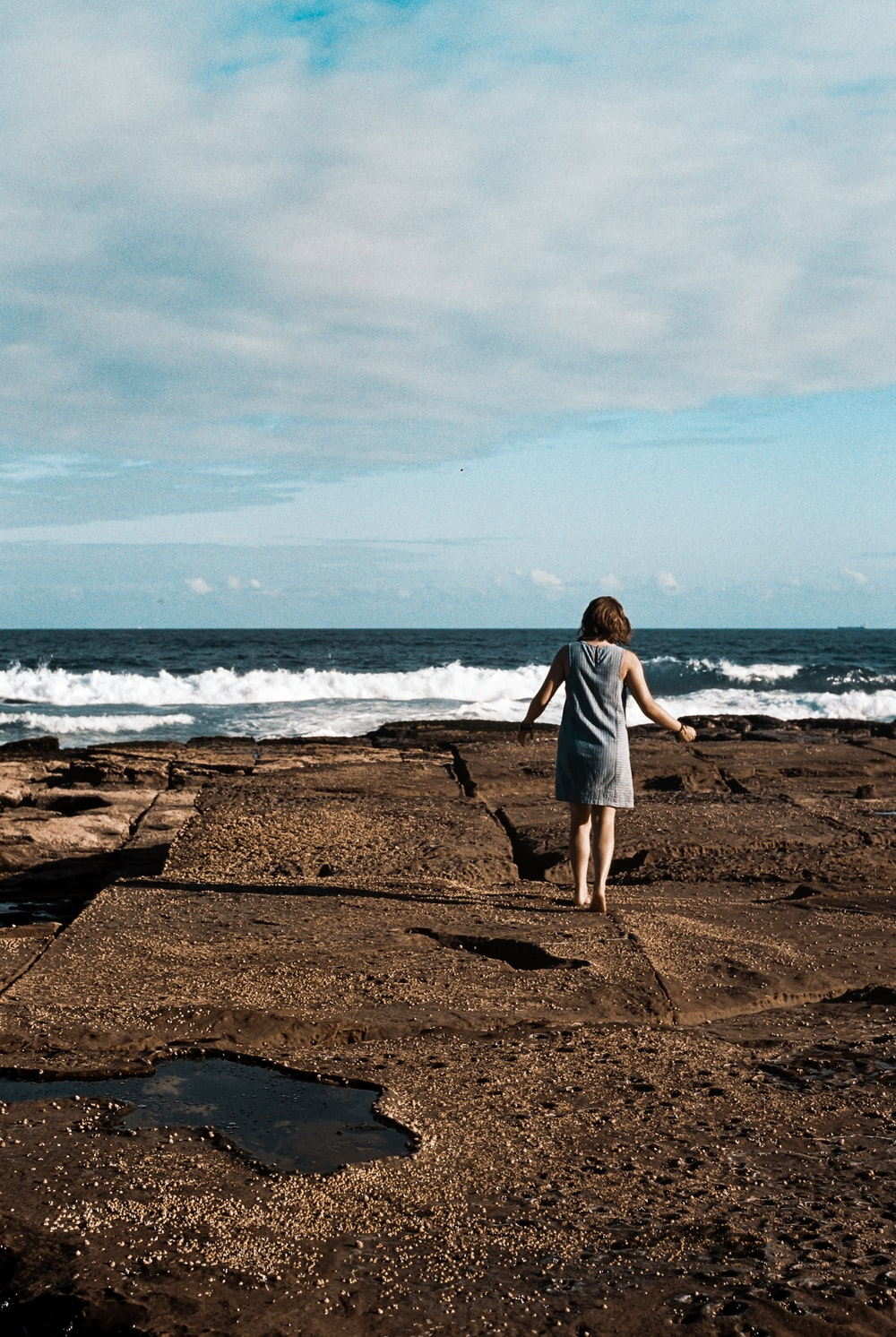 a woman walking on top of black rock formation